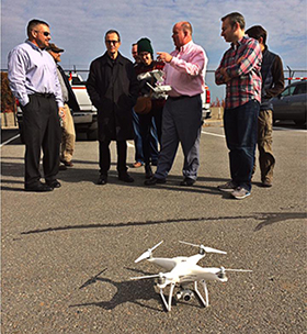 Photo of group of people assembled outdoors with drone in foreground