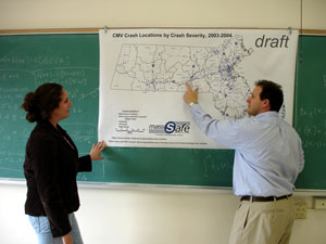 Image of two people discussing map on wall